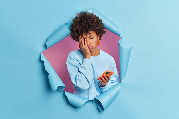 Müde frau satt vom surfen im internet macht gesicht handfläche verwendet moderne smartphone schließt die augen trägt lässigen pullover durch papierwand brechen