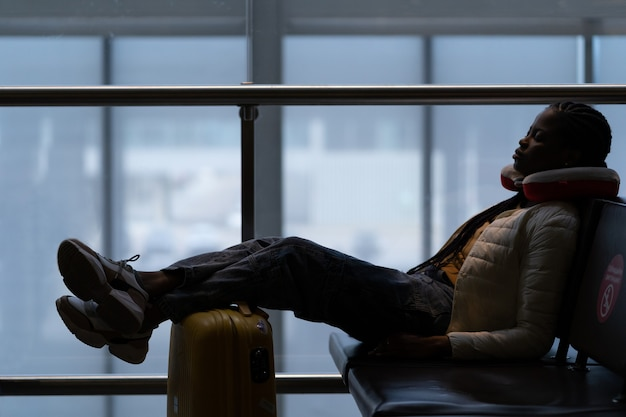 Müde frau schläft im flughafen auf stuhl mit beinen auf koffer