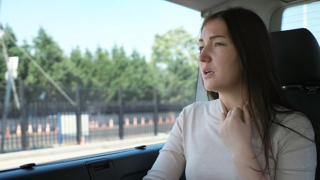 Müde frau schmachtet vor heißem wetter und passt den weißen pulloverhals an, der mit dem auto in der touristischen stadt in der nähe reist