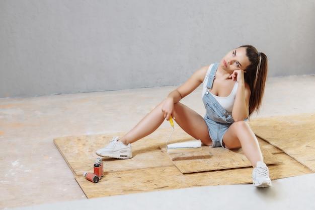 Müde frau sitzt auf flore, während wände mit rolle zu hause malen. reparaturkonzept