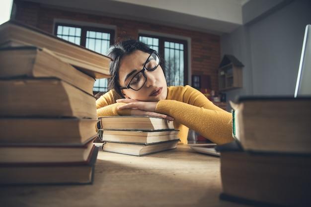 Müde frau und buch mit computer auf dem tisch