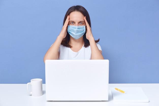 Müde freiberufler arbeiten am laptop, halten die hände auf dem kopf, hat viel arbeit, erschöpftes mädchen posiert isoliert auf blau. fernarbeitskonzept.