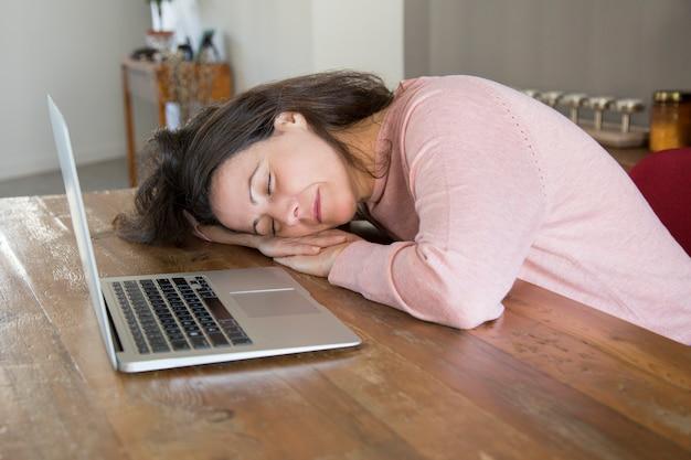 Müde freiberufliche frau, die auf tabelle schläft