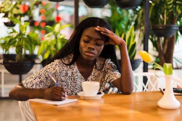 Müde gemischte rasse jugendlich mädchen, die notizen während des studierens machen, mit laptop in der cafeteria, panorama mit kopierraum
