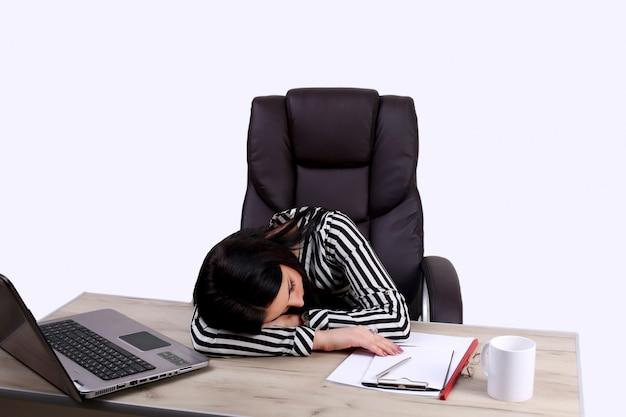 Müde geschäftsfrau, die am laptop arbeitet.