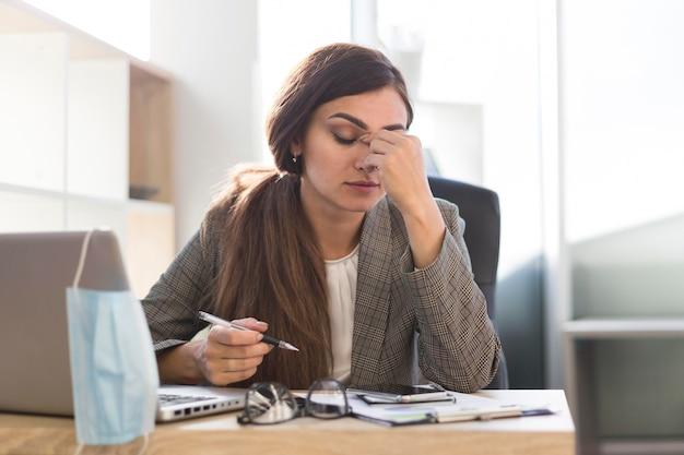 Müde geschäftsfrau, die am schreibtisch mit laptop arbeitet