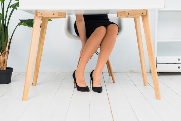 Müde geschäftsfrau, die am tisch sitzt