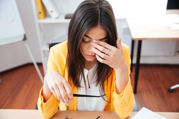 Müde geschäftsfrau, die an ihrem arbeitsplatz im büro sitzt