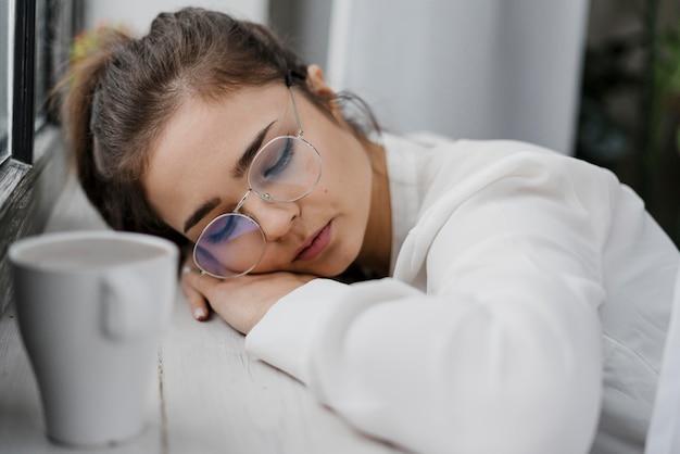 Müde geschäftsfrau, die auf einem fensterbrett ruht