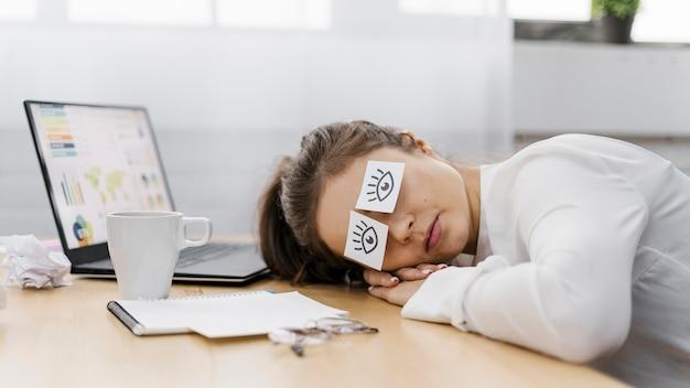 Müde geschäftsfrau, die ihre augen mit gezeichneten augen auf papier bedeckt