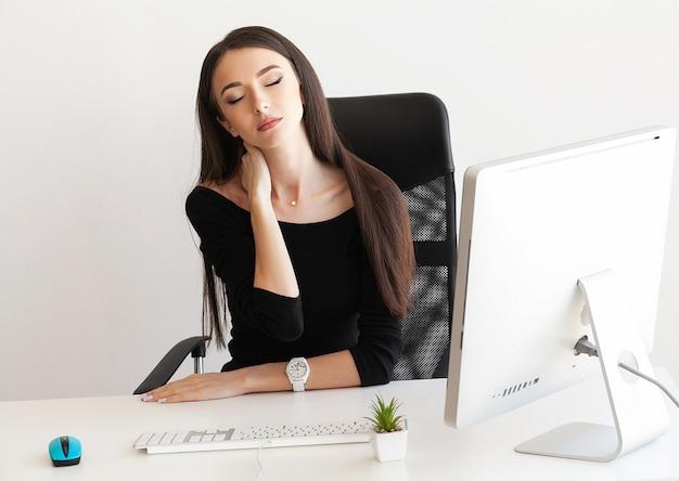 Müde geschäftsfrau, die ihren stutzen anhält