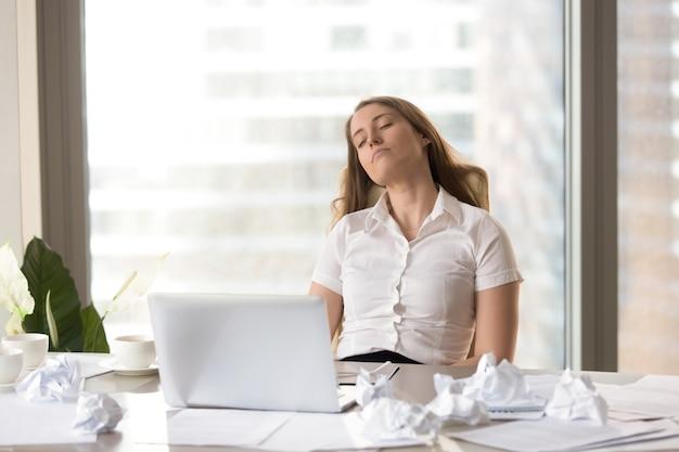 Müde geschäftsfrau, die im stuhl am schreibtisch schläft
