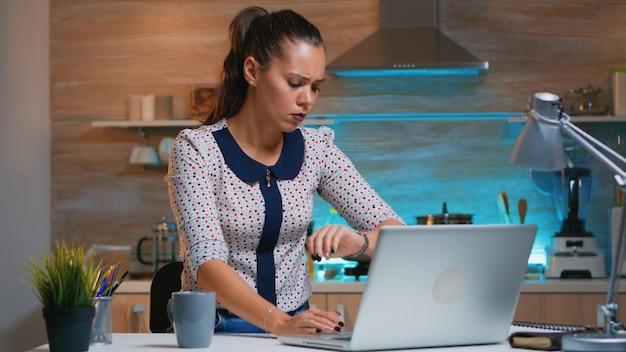 Müde geschäftsfrau, die in der modernen küche überstunden macht und zu hause kaffee trinkt. beschäftigter, fokussierter mitarbeiter, der moderne drahtlose überarbeitung des netzwerks zum lesen von jobs und suchen verwendet.