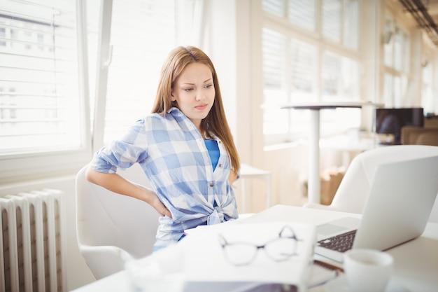 Müde geschäftsfrau, die laptop auf schreibtisch im büro betrachtet