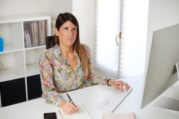Müde geschäftsfrau, die mit computer arbeitet