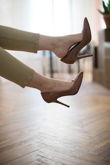 Müde geschäftsfrau, die mit füßen ruht, die braune hochhackige schuhe nach arbeit oder zu fuß ausziehen