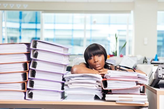 Müde geschäftsfrau, die mit vielen arbeiten im büro am tisch sitzt und nach vorne schaut