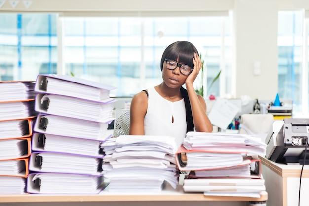 Müde geschäftsfrau, die mit vielen arbeiten im büro am tisch sitzt