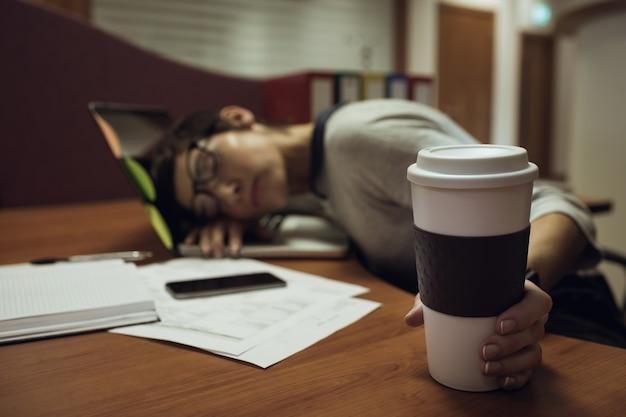 Müde geschäftsfrau, die sich auf schreibtisch lehnt