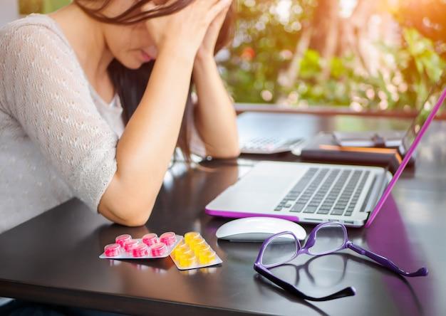 Müde geschäftsfrau hat kopfschmerzen vom bürosyndrom