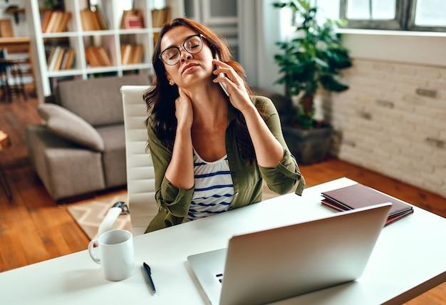 Müde geschäftsfrau im stress arbeitet an einem laptop, während sie zu hause an einem tisch sitzt und telefoniert. freiberuflich, arbeit von zu hause aus.