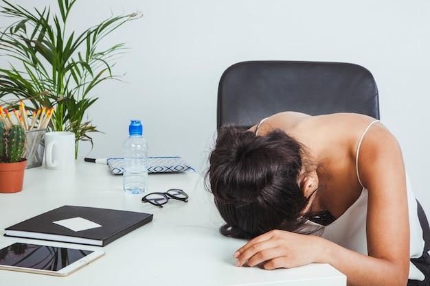 Müde geschäftsfrau legte ihren kopf auf den tisch