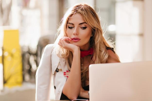 Müde geschäftsfrau mit funkelndem make-up, das laptop-bildschirm beim sitzen im café betrachtet