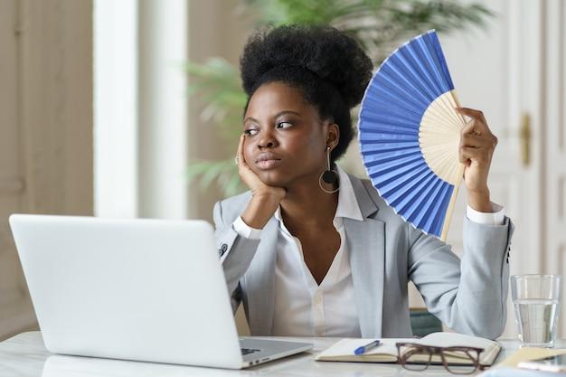 Müde geschäftsfrau winkender papierventilator erschöpft von hitze am arbeitsplatz im büro oder zu hause