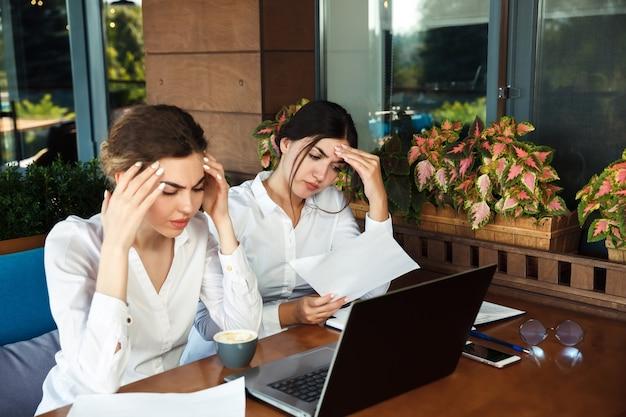 Müde geschäftsfrauen, die kopfschmerzen im büro haben. harte arbeit
