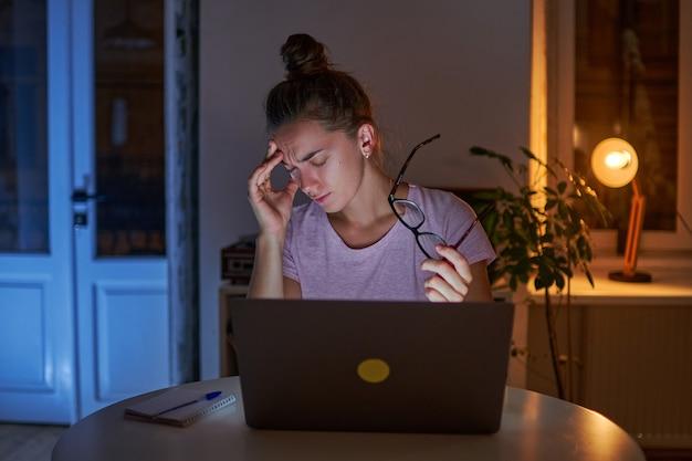 Müde gestresste frau workaholic hält brillen und leidet unter kopfschmerzen, während sitzende späte computerarbeit zu hause
