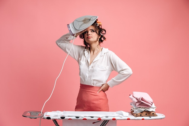 Müde hausfrau bügelt kleidung auf bügelbrett