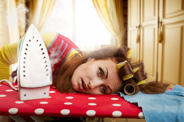 Müde hausfrau mit bügelbrett