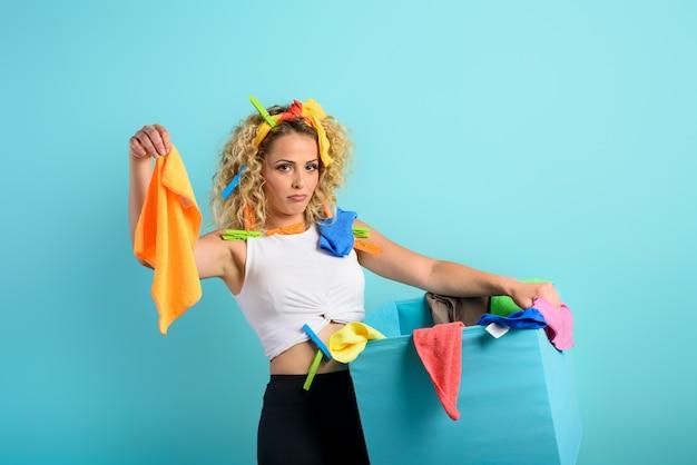 Müde hausfrau voller kleidung und tücher, um den cyanfarbenen hintergrund zu reinigen