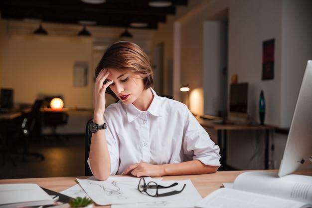Müde hübsche junge geschäftsfrau, die im büro sitzt und kopfschmerzen hat