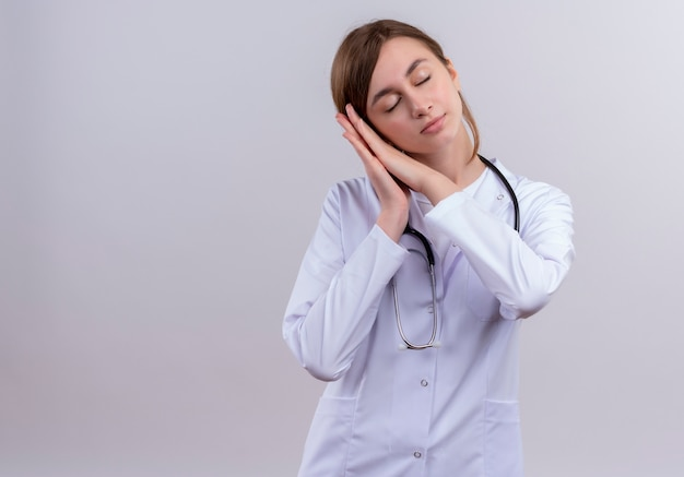 Müde junge ärztin, die medizinische robe und stethoskop trägt, die schlafgeste auf isolierter weißer wand mit kopienraum tun