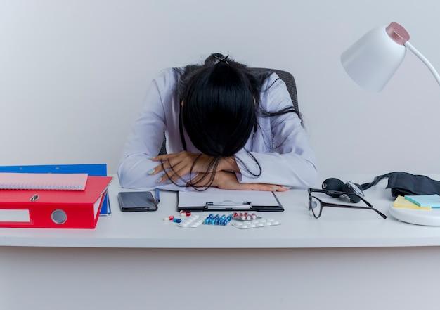 Müde junge ärztin, die medizinische robe und stethoskop trägt, sitzt am schreibtisch mit medizinischen werkzeugen, die hände auf schreibtisch setzen und kopf auf hände lokalisiert