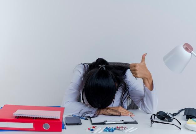 Müde junge ärztin, die medizinische robe und stethoskop trägt, sitzt am schreibtisch mit medizinischen werkzeugen, die hand auf schreibtisch setzen und kopf auf hand zeigen daumen oben isoliert