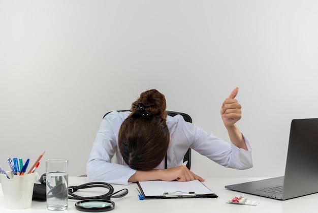 Müde junge ärztin, die medizinische robe und stethoskop trägt, sitzt am schreibtisch mit medizinischen werkzeugen und laptop, der kopf auf schreibtisch setzt, der daumen oben isoliert zeigt