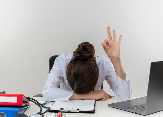 Müde junge ärztin, die medizinische robe und stethoskop trägt, sitzt am schreibtisch mit medizinischen werkzeugen und laptop, die kopf auf schreibtisch setzen, ok-zeichen lokalisiert auf weißer wand