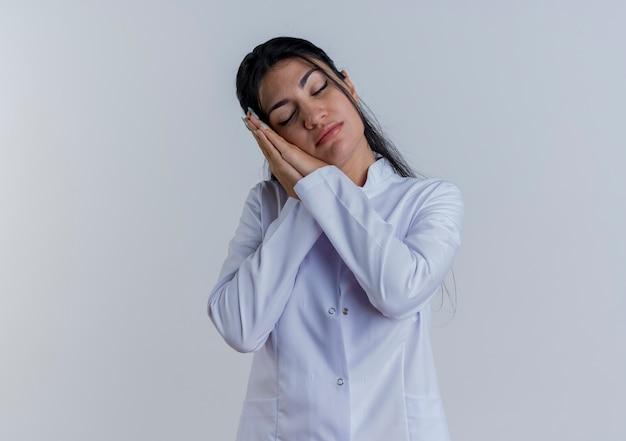 Müde junge ärztin im medizinischen gewand, die schlafgeste mit geschlossenen augen tut, isoliert