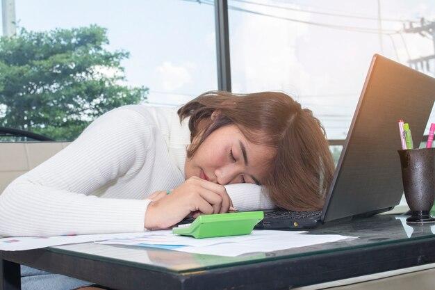 Müde junge asiatische geschäftsfrau, die im büro schläft