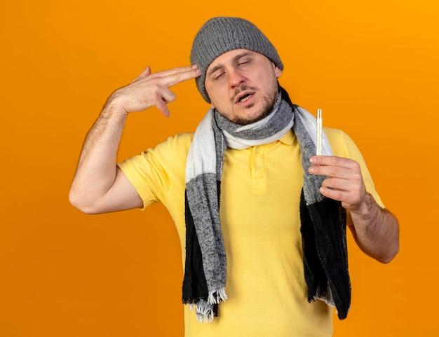 Müde junge blonde kranke slawische mann mit wintermütze und schal gestikuliert pistole handzeichen