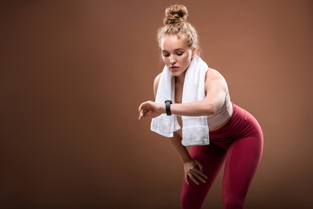 Müde junge blonde sportlerin in activewear, die fitbit an ihrem handgelenk anschaut, während sie schwierige körperliche übungen auf braun macht