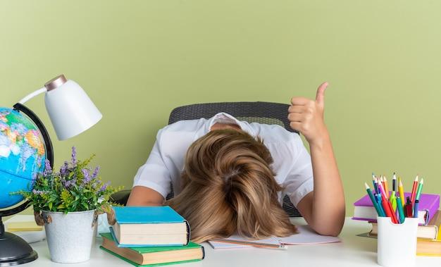 Müde junge blonde studentin sitzt am schreibtisch mit schulwerkzeugen und legt den kopf auf den schreibtisch und zeigt den daumen isoliert auf olivgrüner wand
