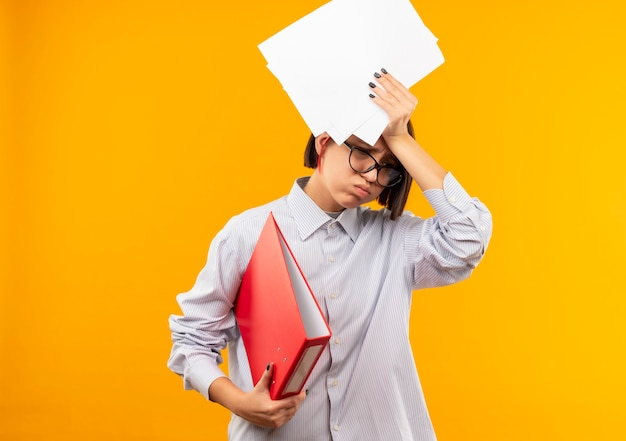 Müde junge call-center-mädchen tragen brille hält ordner und dokumente über kopf nach unten isoliert auf orange wand