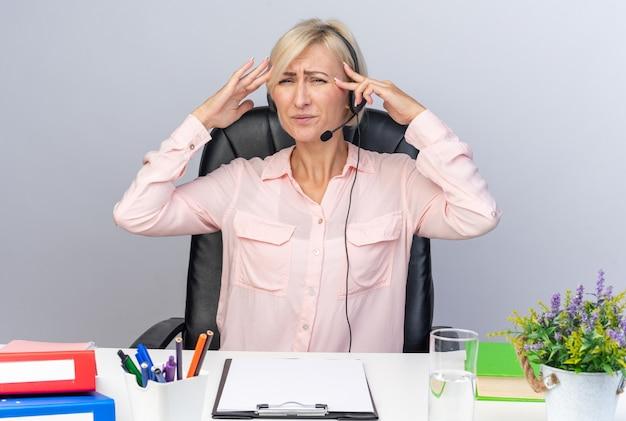 Müde junge callcenter-betreiberin mit headset am tisch sitzend mit bürowerkzeugen, die den finger auf den tempel legen, isoliert auf weißer wand