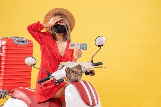 Müde junge dame auf moped mit rotem koffer mit ticket, der die hand auf den kopf legt