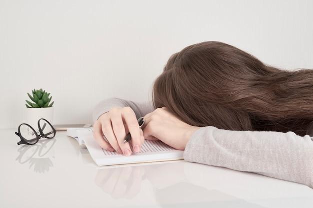 Müde junge frau, die am tisch mit büchern schläft