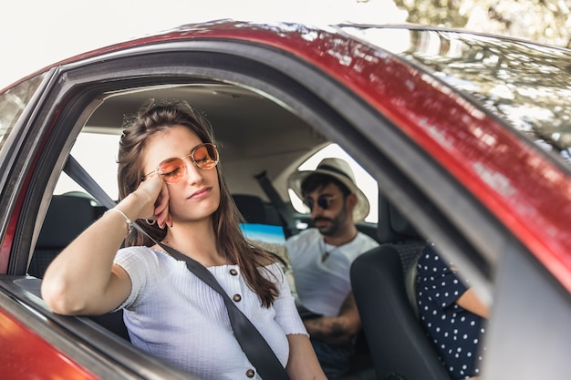 Müde junge frau, die im auto mit ihren freunden schläft