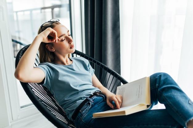 Müde junge frau mit buch, die zu hause auf einem liegestuhl schläft